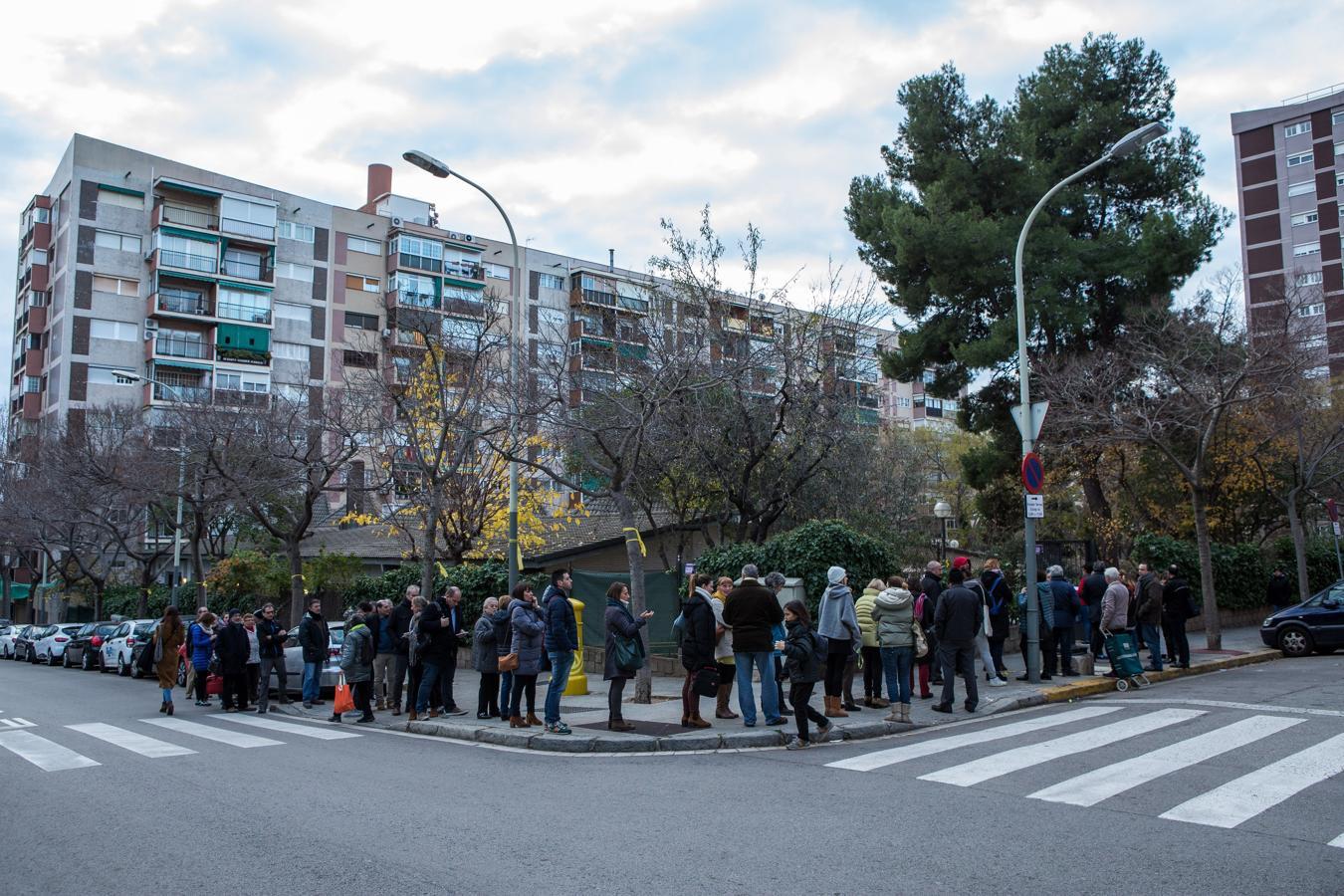 Una fila de ciudadanos esperan para votar en el exterior del colegio electoral Narcís Monturió de Barcelona