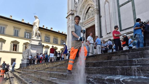 Un operario municipal limpia la escalinata de la basílica de Santa Croce en Florencia