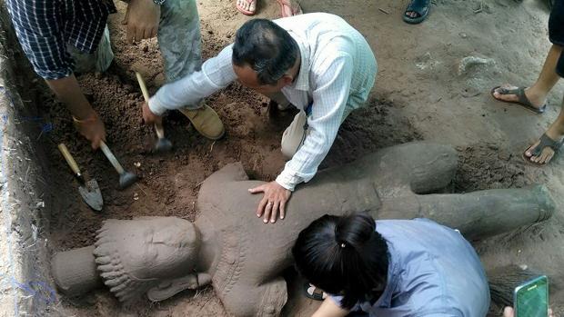 Arqueólogos desenterrando la estatua en el complejo monumental de Angkor
