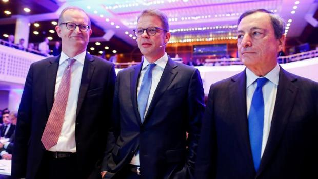 (De izda a dcha: El CEO del Commerzbank, Martin Zielke, junto a su homólogo del Deutsche Banki, Chirstian Sewing y el presidente del BCE, Mario Draghi