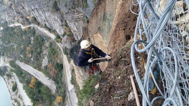 Un operari realitza treballs d'instal·lació en el vessant de Cortes de Pallás