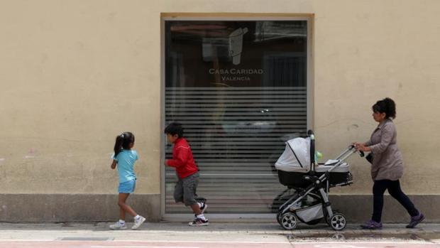 Una familia pasa junto al comedor social de Cáritas en Valencia