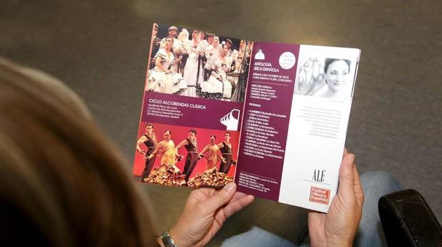Una mujer revisa el programa del festival de música española en Alcobendas