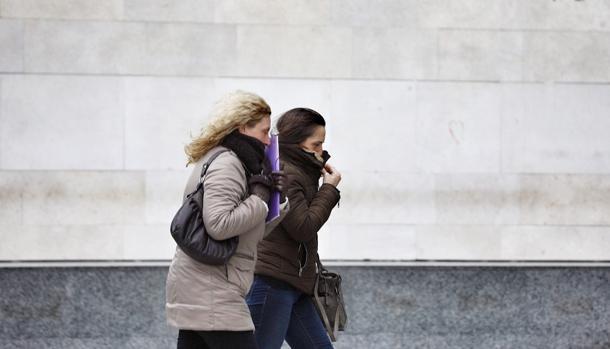 Dos mujeres abrigadas se protegen de los efectos del frio