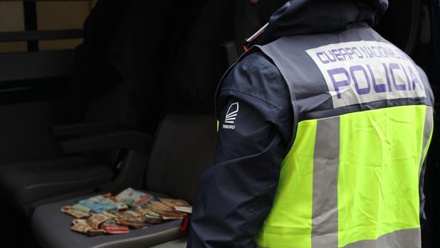 Un agente de la Policía Nacional con dinero intervenido en una operación, en imagen de archivo