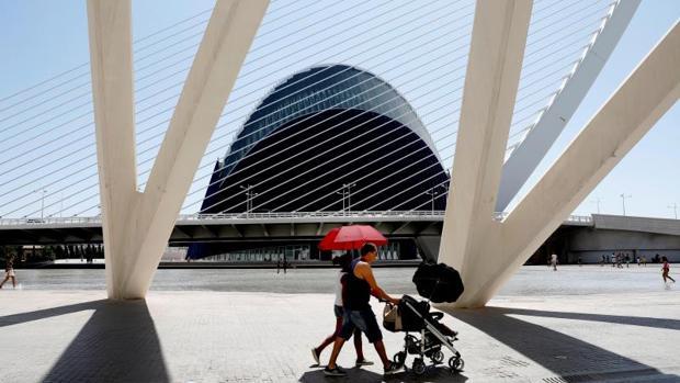 Una pareja se protege con paraguas del sol en el Ágora de la Ciudad de las Ciencias en Valencia, este fin de semana