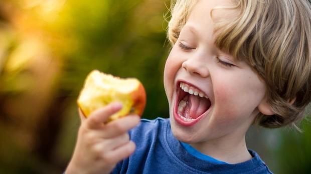 Un niño, comiendo una manzana.