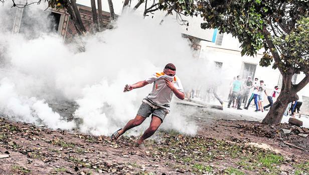 Un manifestante se protege del gas lacrimógeno lanzado por las Policía marroquí