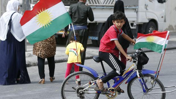 Un niño kurdo monta en una bici decorada con banderas kurdas frente a un centro electoral en Erbil, en la región autónoma del Kurdistán iraquí