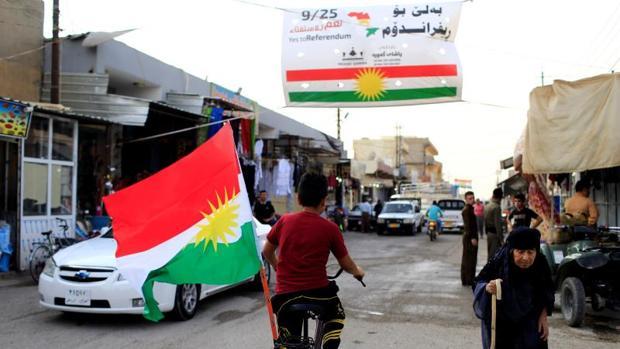 Un niño lleva la bandera kurda en su bicicleta, por Tuz Jurmato