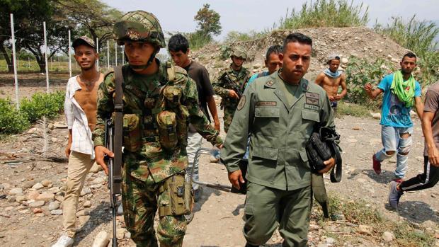 Un soldado colombiano acompaña a uno de los guardias venezolanos que abandonan a Maduro