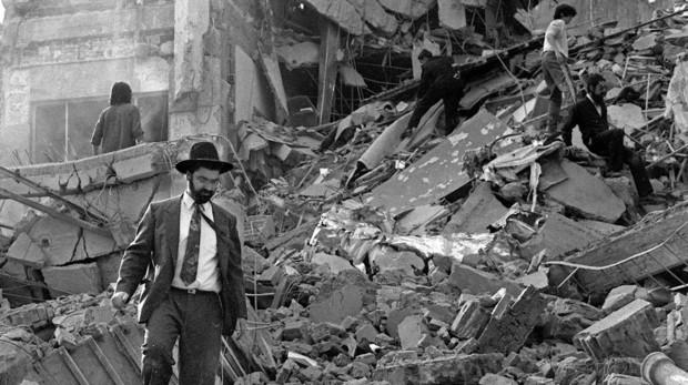 Un hombre camina entre los escombros tras la explosición en el edificio de la Asociación Mutual Israelíta Argentina