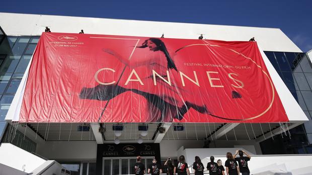 Trabajadores colocan el póster oficial del Festival de Cine de Cannes, que se celebra entre el 17 y el 28 de mayo