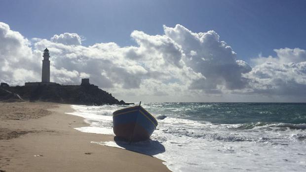 Una patera de madera, utilizada normalmente por inmigrantes magrebíes, en la orilla de la playa, al lado del Faro.