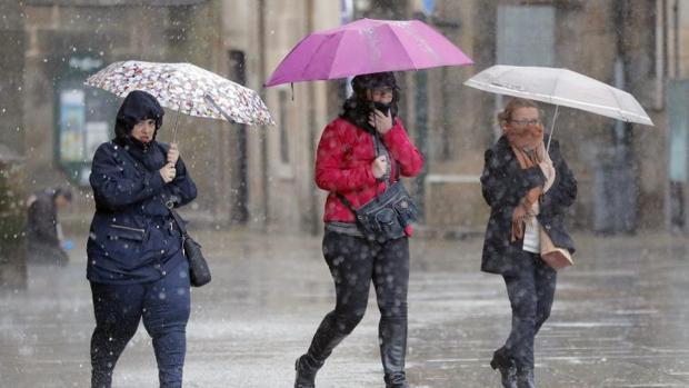 Varias personas transitan bajo la lluvia la plaza del Obradoiro, en Santiago de Compostela