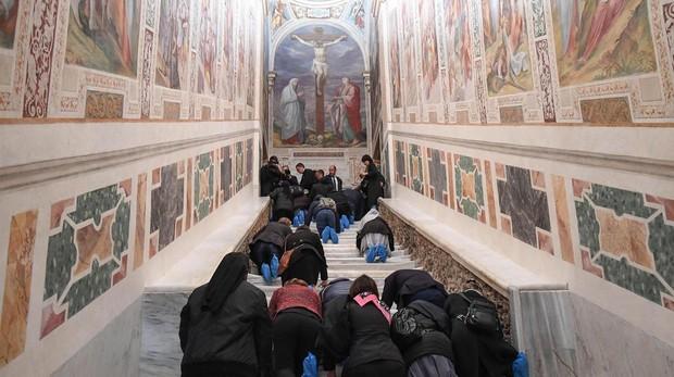 Varias personas recorren de rodillas la Escalera Santa durante su apertura extraordinaria, este jueves en la Basílica de San Juan de Letrán, Roma (Italia)